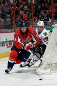 Tyson Strachan of the Washington Capitals battles for the puck against Bryan Bickell of the Chicago Blackhawks in the third period during an NHL game...