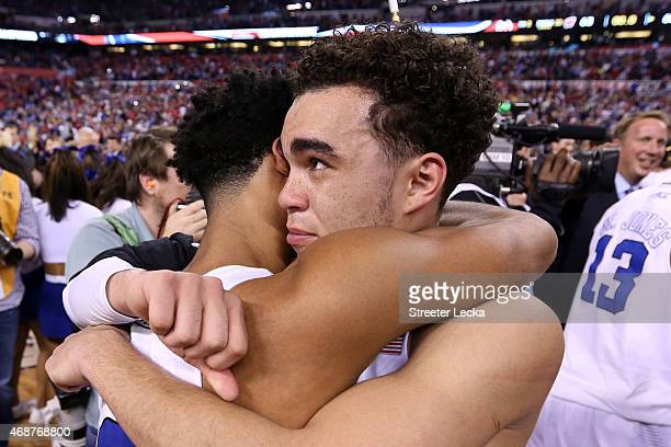 Tyus Jones and Quinn Cook of the Duke Blue Devils celebrate after defeating the Wisconsin Badgers during the NCAA Men's Final Four National...