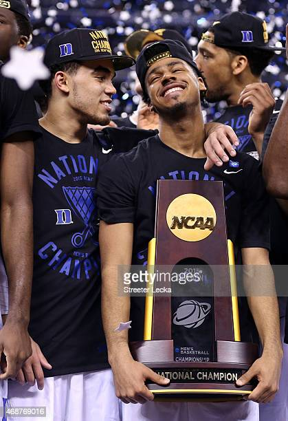 Tyus Jones and Quinn Cook of the Duke Blue Devils celebrate with the championship trophy after defeating the Wisconsin Badgers during the NCAA Men's...