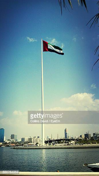 Uae Flag At Seaside With City In Background