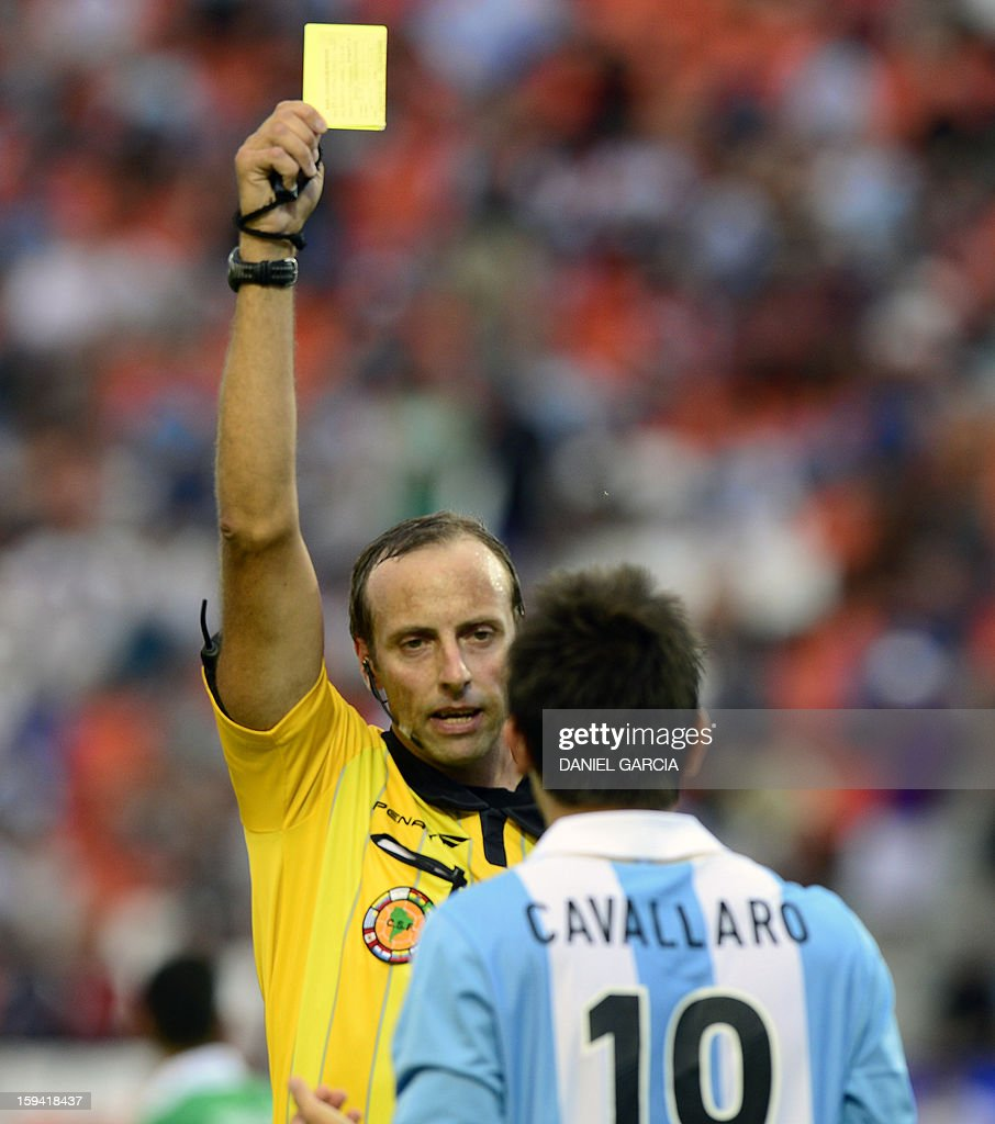 Uauguay's referee Daniel Fedorczuk shows the yellow card to Argentina's midfielder Juan Ignacio Cavallaro during their Group A South American U-20 qualifier football match against Bolivia at Malvinas Argentinas stadium in Mendoza, Argentina, on January 13, 2013. Four teams will qualify for the FIFA U-20 World Cup Turkey 2013. AFP PHOTO / DANIEL GARCIA