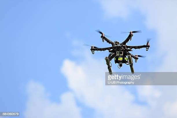Uav drone flying with camera at blue cloudy sky