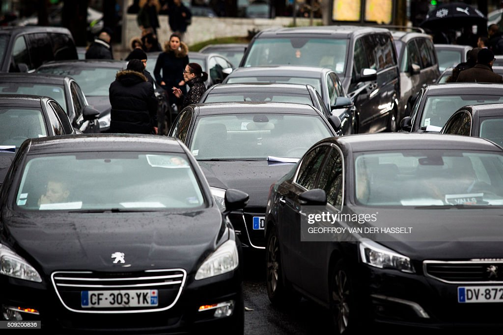 Uber and other ride-hailing companies, known in France as 'voitures de tourisme avec chauffeur' (VTC), a class of companies that allow passengers to book rides with independent professional chauffeurs, gather as they block the roundabout at Place de la Nations to protest against the LOTI law in Paris, on February 9, 2016. / AFP / Geoffroy Van der Hasselt