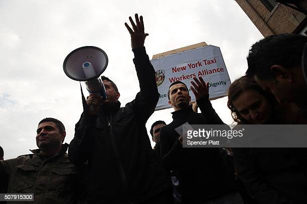 Uber driver representitives speak to hundreds of Uber drivers as they protest the company's recent fare cuts and went on strike in front of the car...
