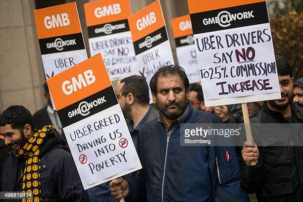 Uber drivers hold up signs during a protest against a rise in the commission taken by Uber Technologies Inc outside their offices in London UK on...
