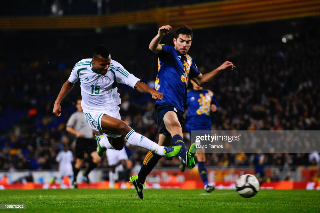 Uche Ikechukwu (L) of Nigeria shoots towards goal under a challenge by Jordi Amat of Catalonia during a friendly match between Catalonia and Nigeria at Cornella-El Prat Stadium on January 2, 2013 in Barcelona, Spain.
