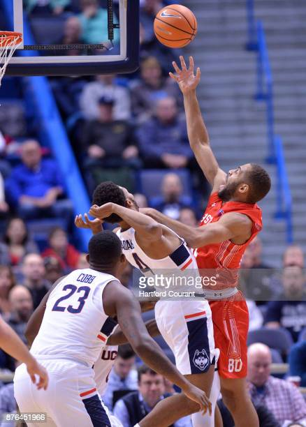 UConn's Jalen Adams defends as Boston University's Cedric Hankerson drives the hoop and UConn's Eric Cobb looks on in the first half on Sunday Nov 19...