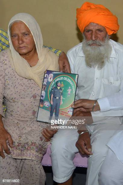 Udham Singh and his wife Gurinder Kaur father and mother of Indian army soldier Paramjeet Singh cry as they hold a picture of their son at their...