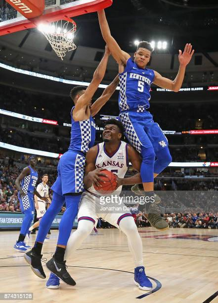 Udoka Azubuike of the Kansas Jayhawks is fouled as he tries to shoot between Sacha KilleyaJones and Kevin Knox of the Kentucky Wildcats during the...