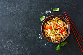 Udon noodles and vegetables served in the clay pot on a black stone background