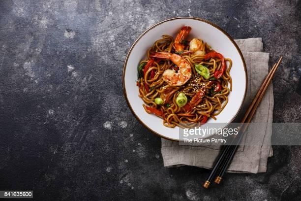 Udon noodles stir-fried with Tiger shrimps and vegetable in bowl on dark background copy space