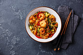 Udon stir-fry noodles with shrimp in bowl and chopsticks on dark stone background copy space