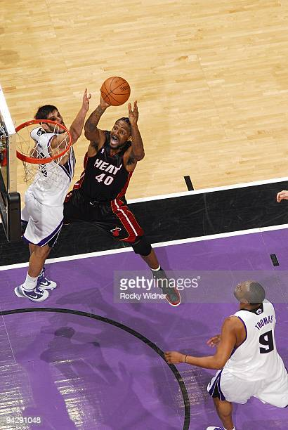Udonis Haslem of the Miami Heat goes up for a shot against Omri Casspi and Kenny Thomas of the Sacramento Kings during the game at Arco Arena on...