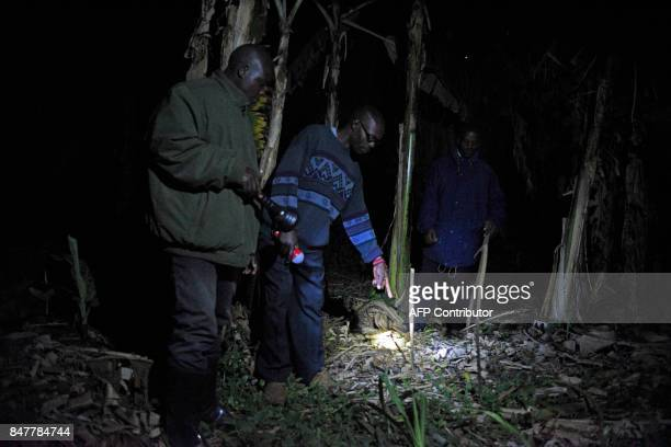 Uganda police officials and Mayumba Kumi crime preventers a community patrol team that was started by the Katabi Town Council inspect the scene of a...