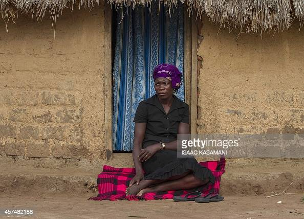 FALLON Ugandan Janet Akiding a victim of domestic violence sits on September 25 2014 at the doorway of her fathers homestead in Bukedea district...