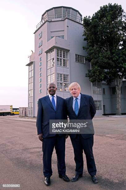Ugandan Minister of Foreign Affairs Sam Kahamba Kutesa poses with British Foreign Secretary Boris Johnson upon his arrival at the Entebbe...