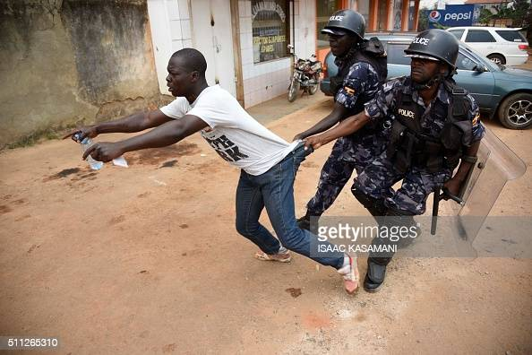 Ugandan policemen arrests a protester on February 19 2016 in Kampala as presidential and parliamentary votes were disrupted in the capital by the...