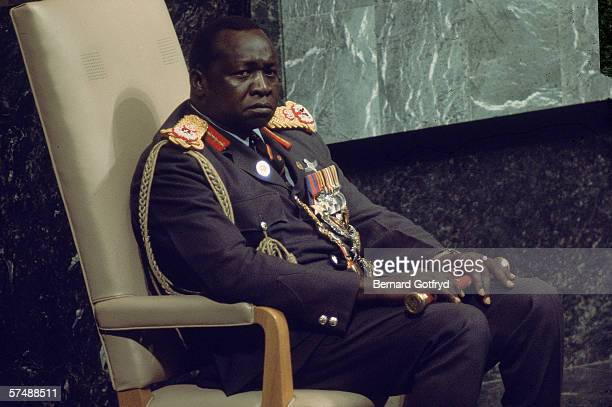 Ugandan President Idi Amin holds a short baton the insignia of rank for a Field Marshal on his lap during a visit to the United Nations to address...