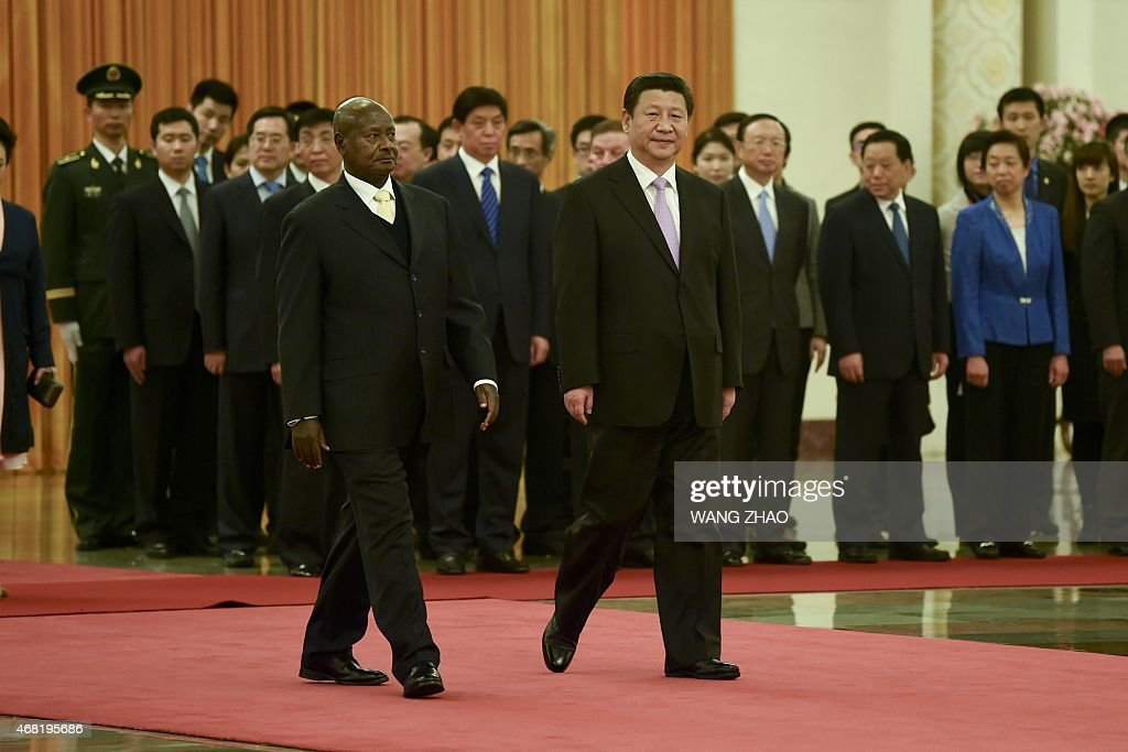 Ugandan President Yoweri Museveni and Chinese President Xi Jinping prepare to inspect Chinese honour guards during a welcome ceremony at the Great...