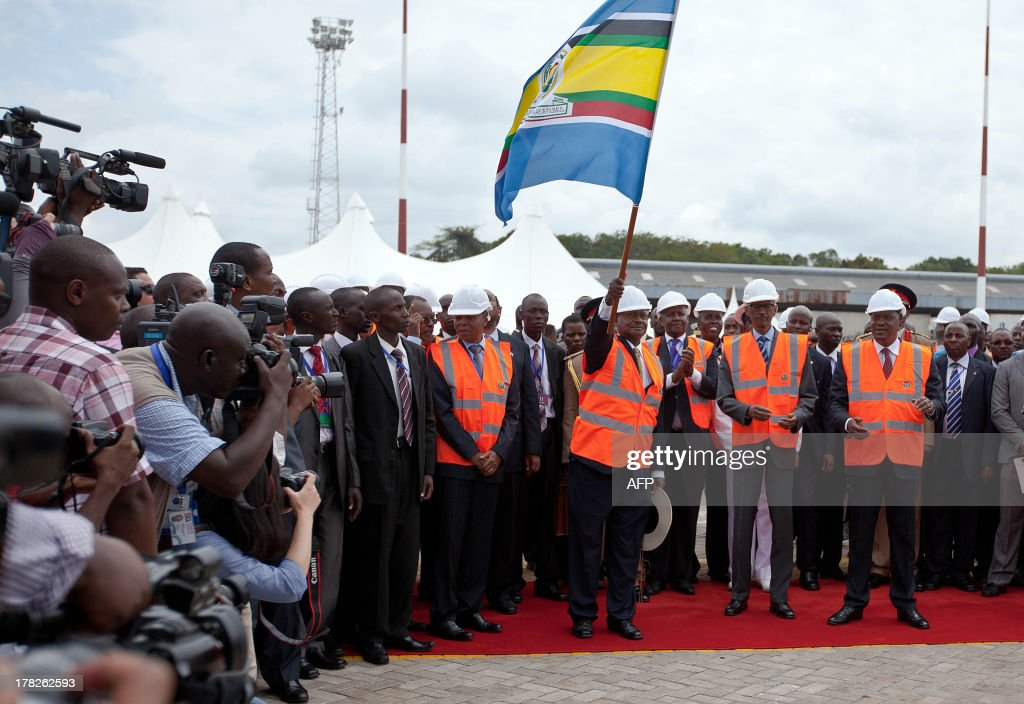 Ugandan President Yoweri Museveni (L) waves a an East African community flag alongside Paul Kagame of Rwanda (C), and Kenya's Uhuru Kenyatta (R) during the inauguration of Berth No. 19 at the Mombasa Port on August 28, 2013.It is the deepest Berth in East Africa with a depth of 13.5 metres. It will help handle cargo capacity ships boosting the economy throughout East Africa.