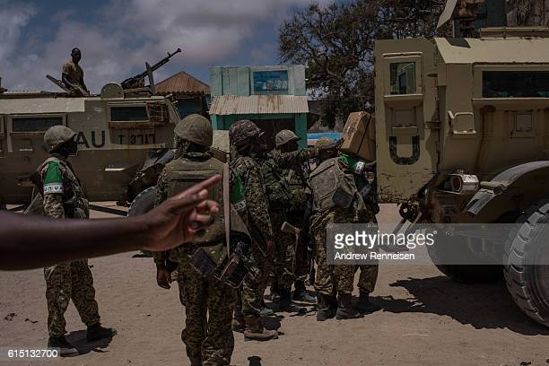 Ugandan troops deployed with the African Union Mission in Somalia load vehicles with supplies before returning to their forward operating base on...