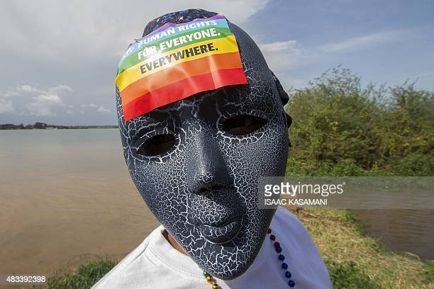 A Ugandan wearing a mask with a rainbow sticker takes part in the Gay Pride parade in Entebbe on August 8 2015 Ugandan activists gathered for a gay...