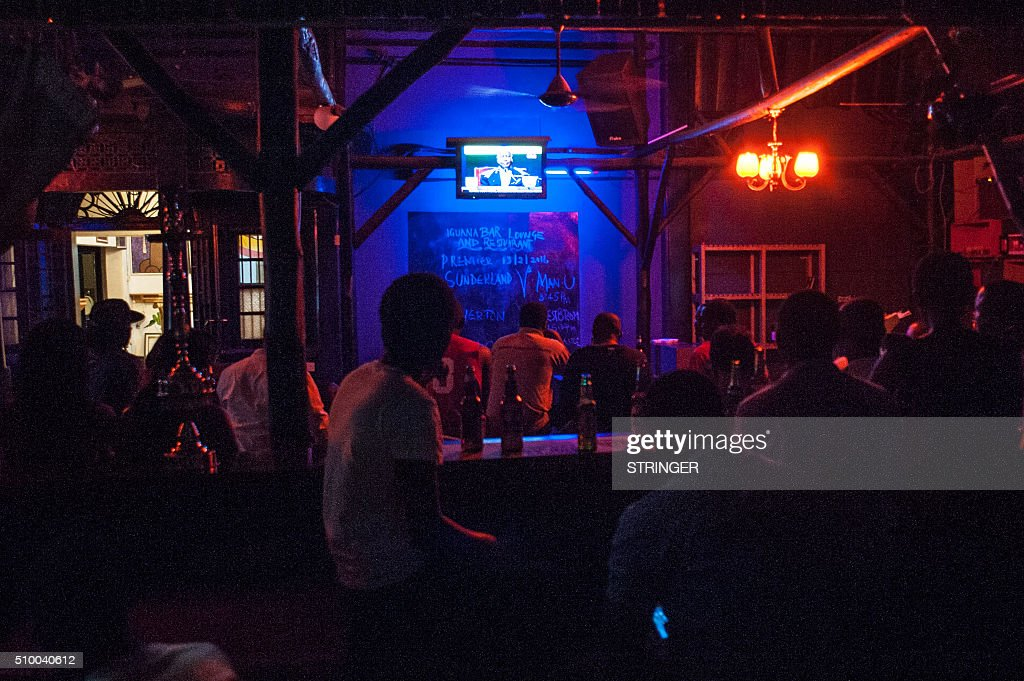 Ugandans watch the 2016 presidential debate live on TV in a bar in Kololo, Kampala, on February 13 2016. Uganda votes in presidential election on February 18, 2016 with seven opposition candidates vying to end Yoweri Museveni's 30-year rule. / AFP / STRINGER