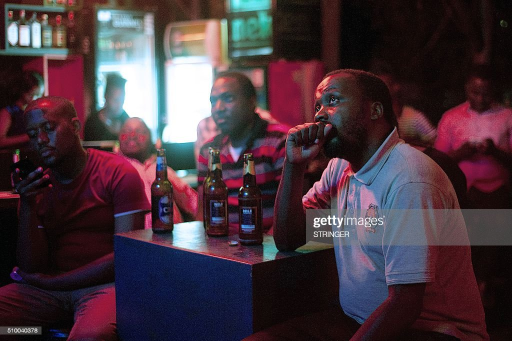 Ugandans watch the 2016 presidential debate live on TV while checking social media feeds in a bar in Kololo, Kampala, on February 13, 2016. Uganda votes in presidential election on February 18, 2016 with seven opposition candidates vying to end Yoweri Museveni's 30-year rule. / AFP / STRINGER