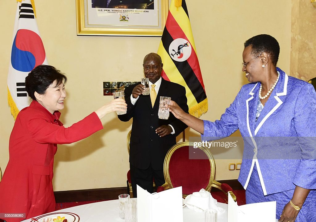 Uganda's President Yoweri Museveni (C), first lady Janet Museveni (R) and South Korea's President Park Geun-Hye (L) drink a toast after a meeting at State House in Entebbe, on May 29, 2016. Museveni vowed to cut military and security ties with North Korea in line with UN sanctions imposed following Pyongyang's nuclear and missile tests, a Seoul official said on May 29. / AFP / -