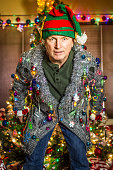 A Caucasian man wearing an ugly cardigan holiday sweater, and an elf hat, with a decorated tree in the background.