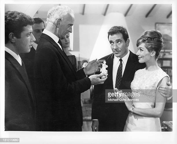 Ugo Tognazzi and Emmanuele Riva with party guests in a scene from the film 'The Hours Of Love' 1963