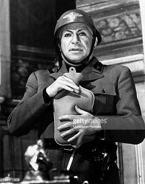 Ugo Tognazzi dressed up as Benito Mussolini keeps in his hands a hot water bottle in a scene from the hilarious comedy Claretta and Ben starring the...