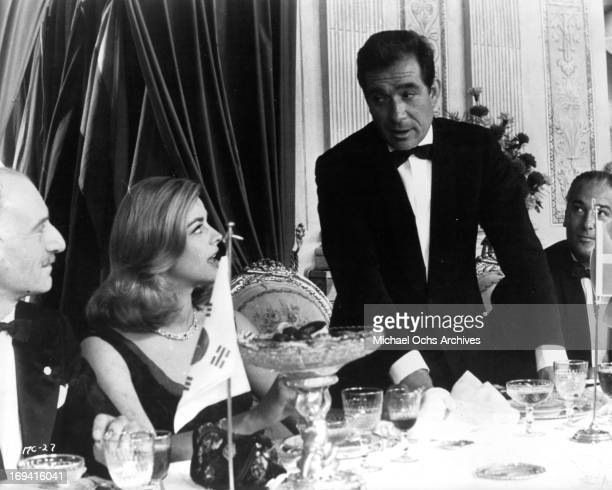 Ugo Tognazzi standing up at table with Gian Maria Volonte Michele Girardon and Jose Luis de Vilallonga in a scene from the film 'The Magnificent...