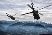 Two flying Sikorsky Uh-60 Black Hawk army helicopters flying towards rocky mountains