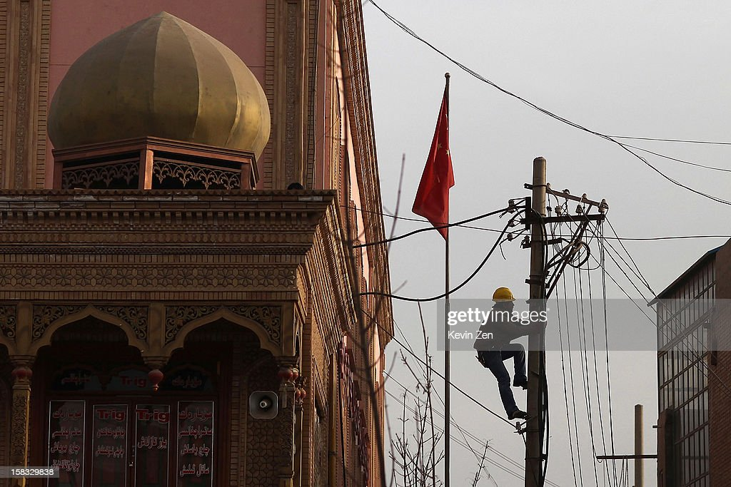 Uighur electrician climbing wire rod repairs line in Kashgar, on December 10, 2012 in Kashi, China. Kashgar is home to the ethnic Uyghur Muslim community.