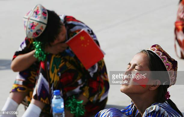 Uighur Muslim students attend the closing ceremony of the 2008 Beijing Olympic Games torch relay the Xinjiang Province leg at People's Park on June...