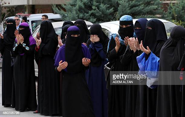 Uighur women offer prayers as Police use pepper spray to prevent the breach of a barricade by Uighur seperatist supporters during a demonstration...