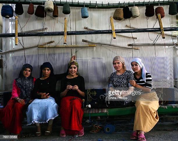 Uigur women take a break of weaving carpets in the Hetian Carpet Factory on September 4 2007 in Hetian of Xinjiang Uygur Autonomous Region China...
