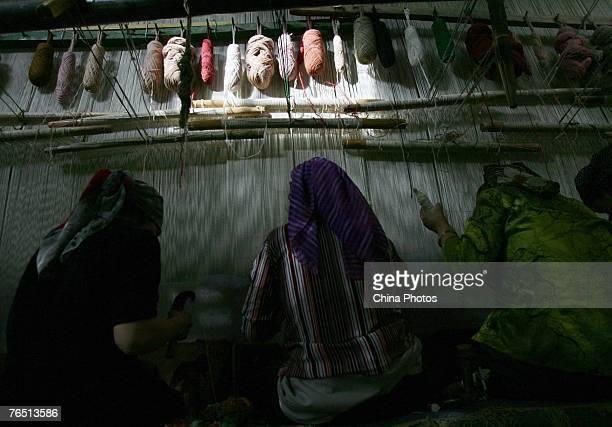 Uigur women weave carpets in the Hetian Carpet Factory on September 4 2007 in Hetian of Xinjiang Uygur Autonomous Region China Hetian nicknamed in...
