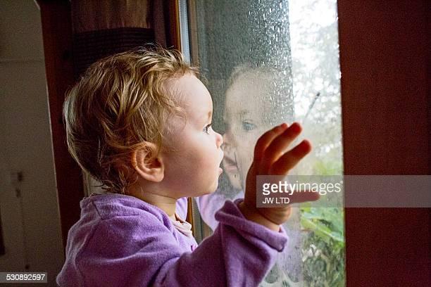 Uk, London, young girl (2-3) watching the rain