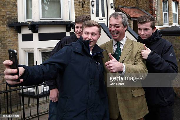 Ukip leader Nigel Farage has a selfie photograph taken with some boys as he canvasses in the Thanet South constituency on April 11 2015 in...