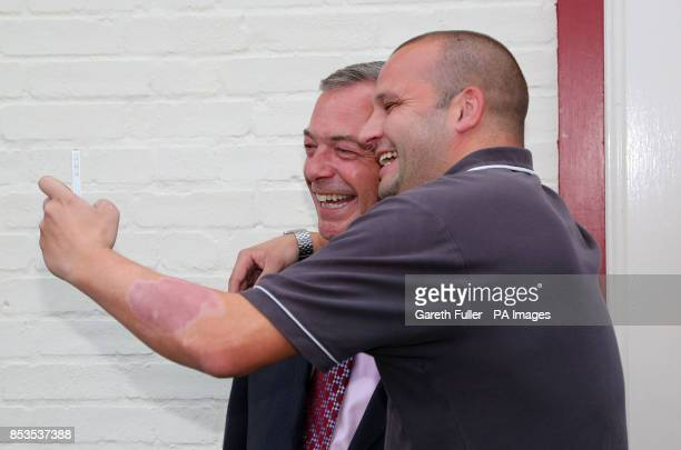 Ukip party leader Nigel Farage poses for a picture with a supporter during a visit to Basildon Essex as his party make gains across the country...