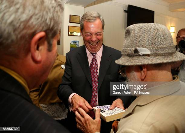 Ukip party leader Nigel Farage signs an autograph during a visit to Basildon Essex as his party make gains across the country following yesterdays...