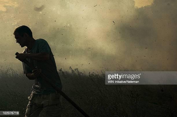 Ukraine, Crimea, Tabachnoye, man fleeing from fire