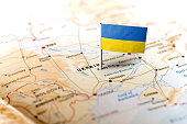 The flag of Ukraine pinned on the map. Horizontal orientation. Macro photography.