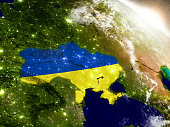Ukraine with embedded flag on planet surface during sunrise. 3D illustration with highly detailed realistic planet surface and visible city lights. 3D model of planet created and rendered in Cheetah3D
