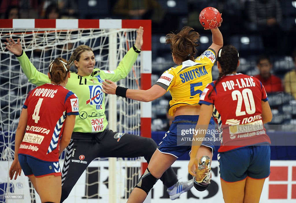 Ukraine's Iryna Shutska Sheyenko scores a goal against Serbia's goalie Katarina Tomasevic (2ndL) during the 2012 EHF European Women's Handball Championship match between their teams on December 6, 2012, at the Kombank Arena of Belgrade. The Serbian capital Belgrade hosts the preliminary round Group A matches including Czech Republic, Norway, Serbia and Ukraine. AFP PHOTO / ATTILA KISBENEDEK