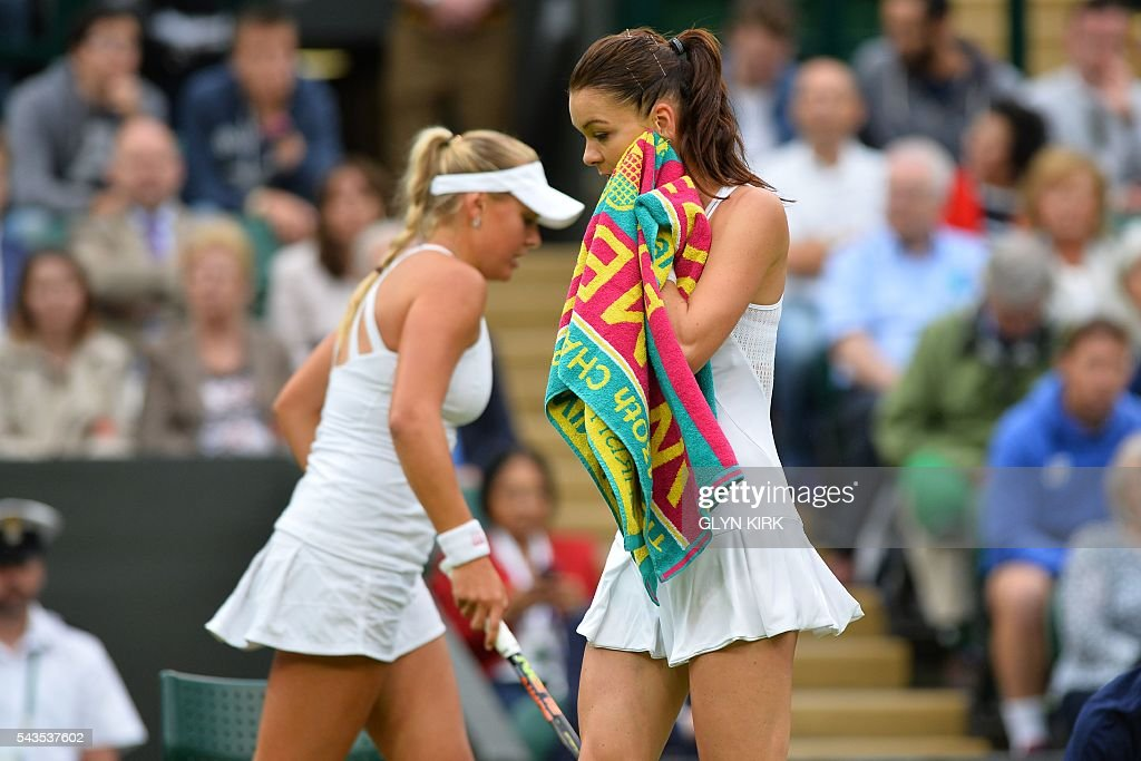 Ukraine's Kateryna Kozlova (L) and Poland's Agnieszka Radwanska (R) change ends during their women's singles first round match on the third day of the 2016 Wimbledon Championships at The All England Lawn Tennis Club in Wimbledon, southwest London, on June 29, 2016. / AFP / GLYN