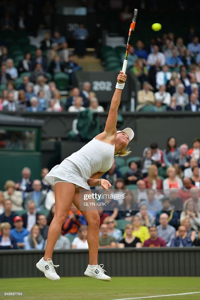 Ukraine's Kateryna Kozlova serves against Poland's Agnieszka Radwanska during their women's singles first round match on the third day of the 2016 Wimbledon Championships at The All England Lawn Tennis Club in Wimbledon, southwest London, on June 29, 2016. / AFP / GLYN