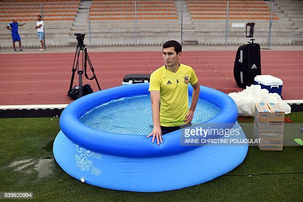Ukraine's midfielder Taras Stepanenko kneels in an inflatable pool of cold water as recovery therapy during a training session at the Carcassonne...